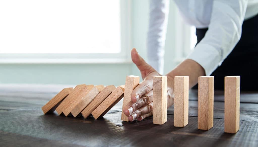 Geschäftsmann stoppt Domino Effekt